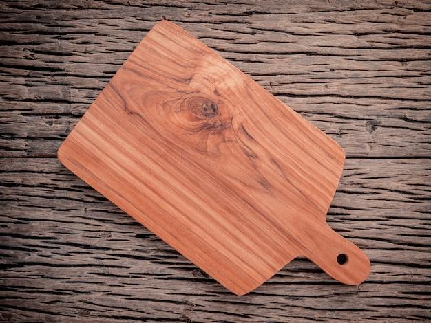 Hölzernes schneidebrett des leeren weinlese teakholzes auf hölzernem lebensmittelhintergrund des schmutzes.