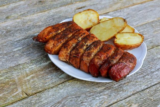 Hölzernes schneidebrett mit gegrilltem filetsteak und kartoffel