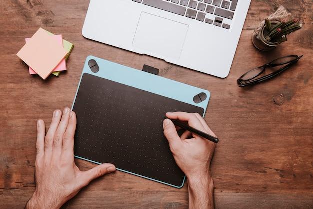 Hölzernes schreibtischkonzept mit den händen, die auf designtablette zeichnen