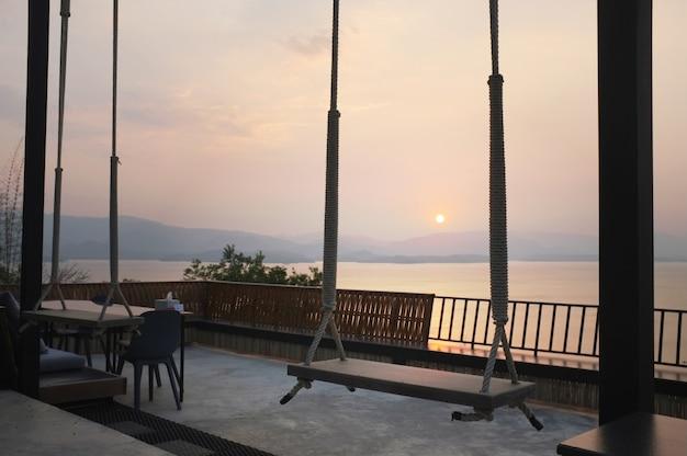 Hölzernes schwingen des schönen sonnenuntergangs auf nationalpark khuean srinagarindra bei kanchanaburi, thailand