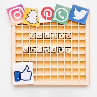 Hölzernes spiel scrabble, das wort des sozialen netzes mit verschiedenen beweglichen app-ikonen zeigt