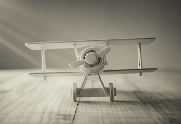 Hölzernes spielzeugflugzeug auf hölzerner tabelle im weinleseton.