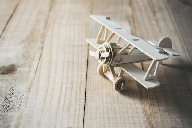 Hölzernes spielzeugflugzeug auf hölzerner tabellenansicht von oben.