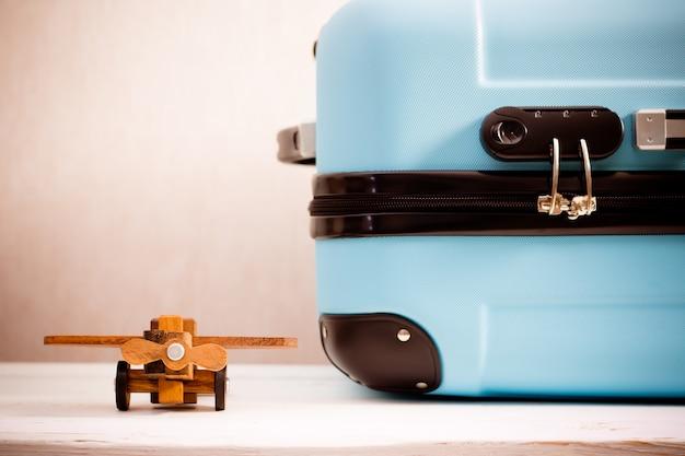 Hölzernes spielzeugflugzeug und koffernahaufnahme. sommerferien und reisekonzept. retro abgeschwächt.