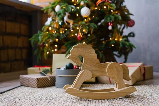 Hölzernes spielzeugpferd auf dem hintergrund eines weihnachtsbaums mit geschenken