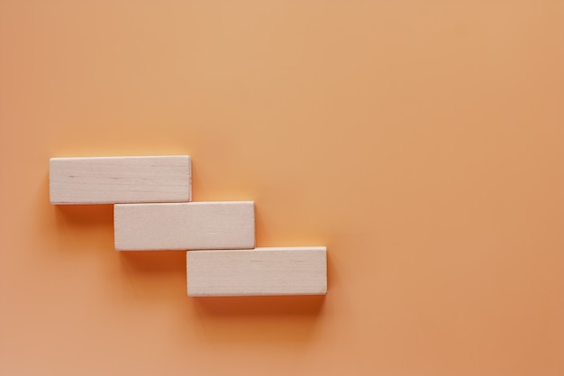 Hölzernes spielzeugtreppenhaus auf beige farbhintergrund für schritt zum zielerfolgskonzept