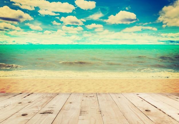 Hölzernes tabellensand-strandmeer und in den himmelwolken mit weinleseton.