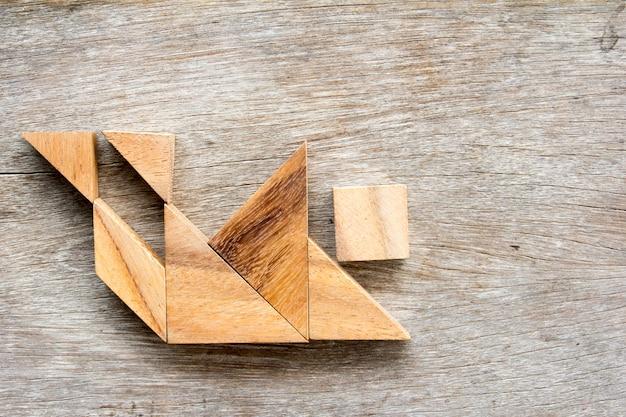 Hölzernes tangram puzzlespiel im menschlichen stolpern und in fallender form