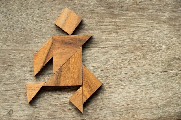 Hölzernes tangrampuzzlespiel als laufender hintergrund des mannes
