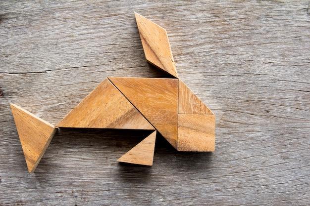 Hölzernes tangrampuzzlespiel im fischformhintergrund