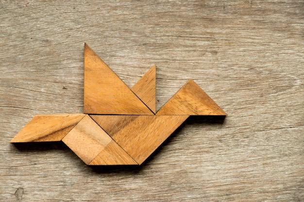 Hölzernes tangrampuzzlespiel im fliegenvogelformhintergrund