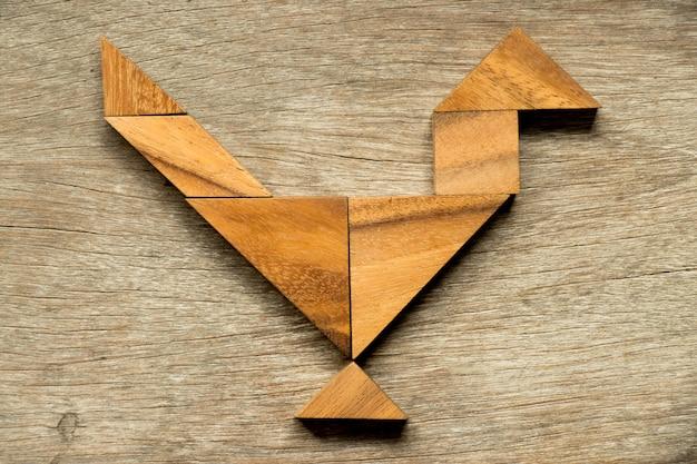 Hölzernes tangrampuzzlespiel im hahn- oder hahnformhintergrund