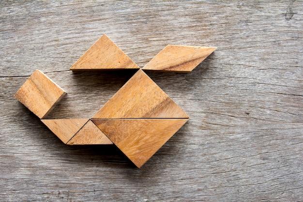Hölzernes tangrampuzzlespiel im hubschrauberformhintergrund