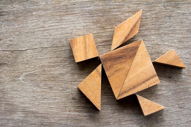 Hölzernes tangrampuzzlespiel im schildkrötenformhintergrund
