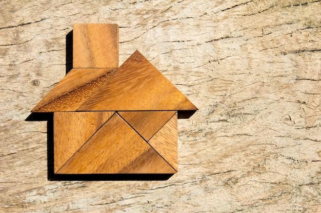 Hölzernes tangrampuzzlespiel in der ausgangsform für traumhaus oder glückliches lebenkonzept