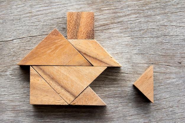 Hölzernes tangrampuzzlespiel warten, um form für bautraumhaus nach hause zu erfüllen