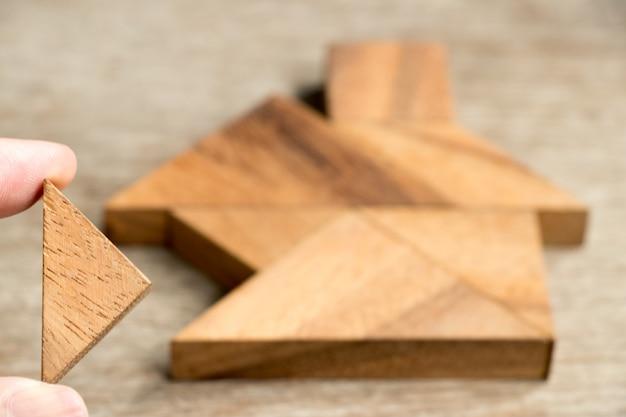 Hölzernes tangrampuzzlespiel warten, um in der hausform für bautraumhauseigentuminvestition zu erfüllen