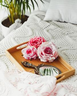 Hölzernes tellersegment mit spiegel und rosafarbenen rosen auf gestrickter decke