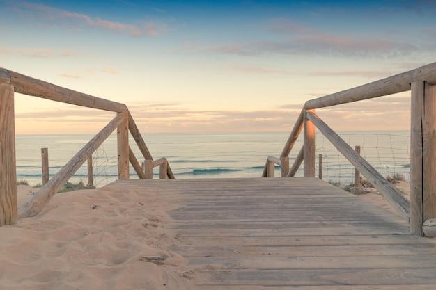 Hölzernes treppenhaus und geländerzugang zum strandsand bei sonnenuntergang