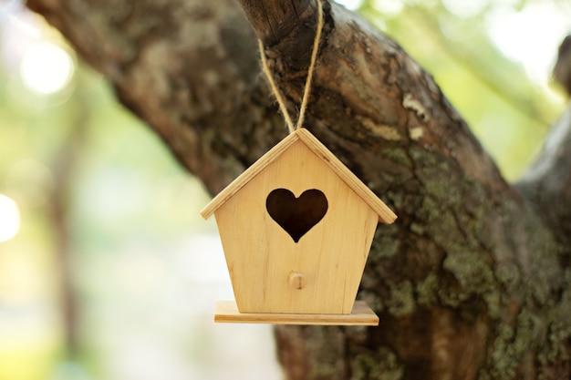 Hölzernes vogelhaus, das vom baum im herbstgarten hängt. konzept für neues zuhause. vogelhaus oder vogelkasten im sommersonnenschein mit natürlichem grünem blatthintergrund.