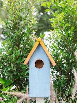Hölzernes vogelnest dekorativ im garten