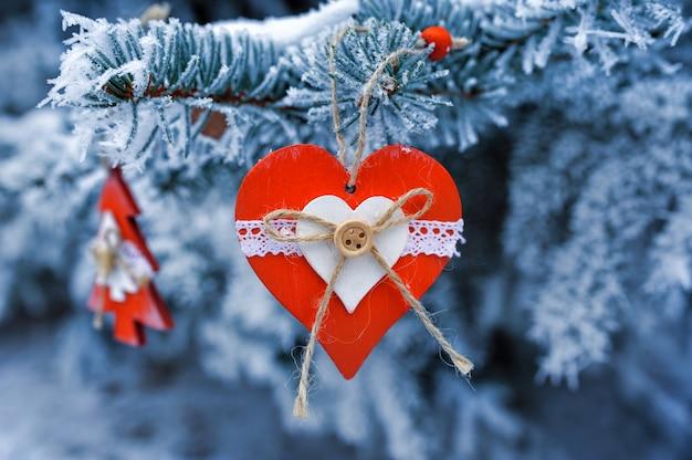 Hölzernes weihnachten spielt auf einem schönen schneebedeckten tannenbaum im winter