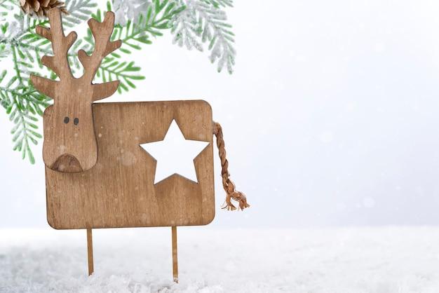 Hölzernes weihnachtshirsch mit tannenbaum auf schnee. weihnachts- oder neujahrskonzept