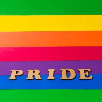 Hölzernes wort des stolzes auf bunter lgbt-flagge