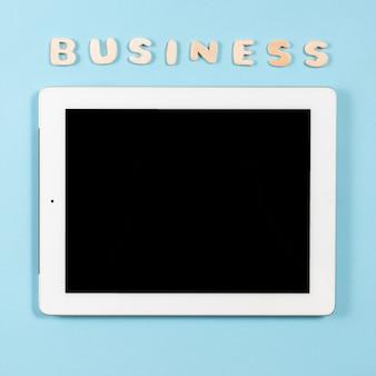 Hölzernes wortgeschäft über der spitze der digitalen tablette gegen blauen hintergrund