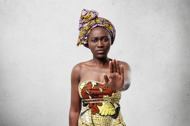 Hör auf! afrikanische frau mit dunkler glatter haut, die traditionelle kleidung trägt, die ihre handfläche zeigt, die verweigert, etwas nicht zu tun. selbstbewusste dunkelhäutige frau, die keine geste zeigt. veto- und nachfragekonzept