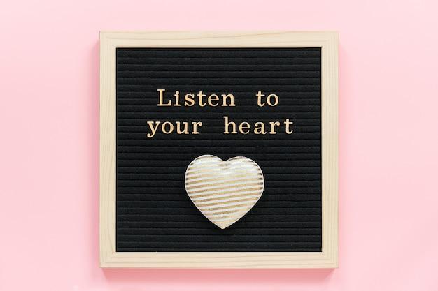 Hör auf dein herz. motivationszitat in goldbuchstaben und dekorativem textilherz auf schwarzem briefbrett auf rosa hintergrund.