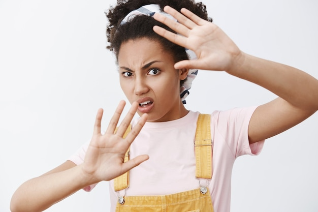 Hör auf, es um mein gesicht zu winken. porträt einer missfallenen und belästigten verärgerten modernen afroamerikanerin in gelbem overall und stirnband, bedeckt mit erhobenen handflächen, stirnrunzeln