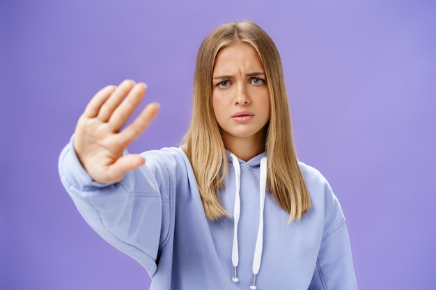 Hör auf mich zu fotografieren. betroffene unzufriedene junge frau, die das ende des schießens fordert, die hand in nein zieht, und ablehnungsgeste, die die stirn runzelt und ernst und unzufrieden über die blaue wand schaut
