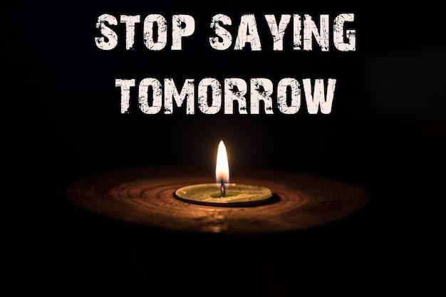 Hör auf, morgen zu sagen - weiße kerze mit dunklem hintergrund - in einem hölzernen kerzenständer.