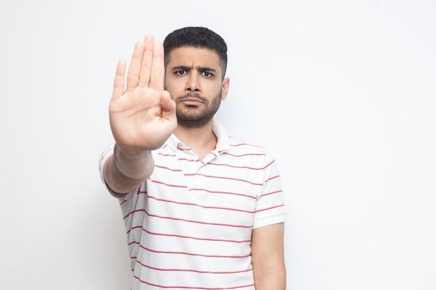 Hör auf. porträt eines wütenden bärtigen jungen mannes im gestreiften t-shirt, der mit der hand der stopp-warngeste steht und die kamera mit ernstem gesicht betrachtet. indoor-studioaufnahme, isoliert auf weißem hintergrund.