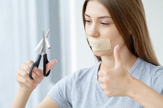 Hör auf zu rauchen, eine frau mit einem versiegelten mund, die eine kaputte zigarette hält