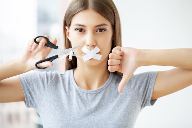 Hör auf zu rauchen, eine frau mit versiegeltem mund schneidet eine zigarette mit einer schere.