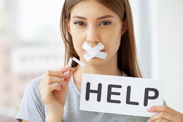 Hör auf zu rauchen, eine junge frau mit einem versiegelten mund, die eine kaputte zigarette hält.