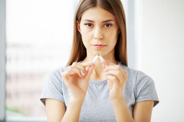 Hör auf zu rauchen, frau hält eine kaputte zigarette in der hand.