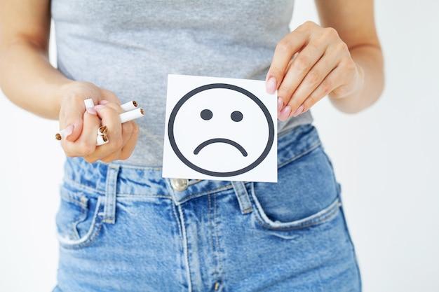 Hör auf zu rauchen, frau hält gebrochene zigaretten in händen und karte mit traurigem lächeln.