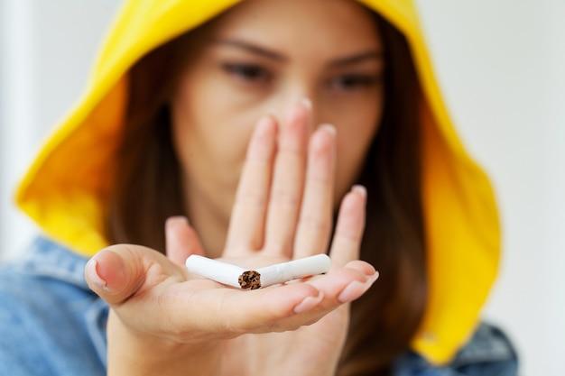 Hör auf zu rauchen, frau hält kaputte zigarette in den händen.