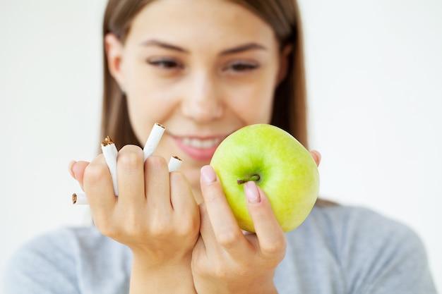 Hör auf zu rauchen, frau hält kaputte zigaretten und grünen apfel in den händen.