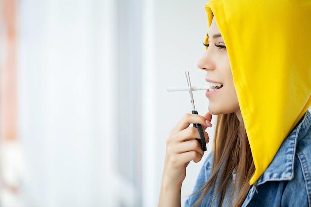 Hör auf zu rauchen, junge frau schneidet eine zigarette mit einer schere.