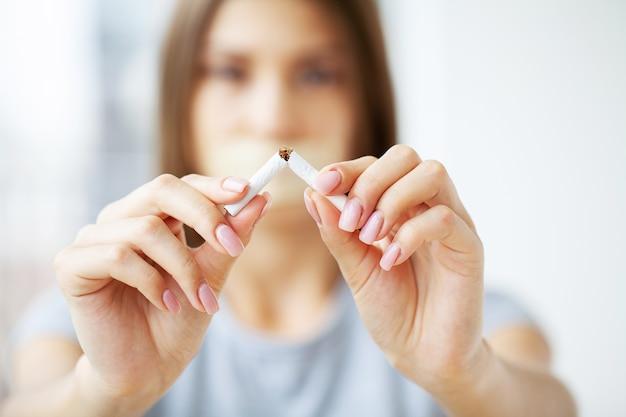 Hör auf zu rauchen, junges mädchen hält kaputte zigarette in den händen.