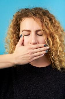 Hör auf zu reden! erschrockene rothaarige lockige süße junge frau mit geschlossenen augen, die ihren mund mit ihrer hand bedecken. negative gefühle.