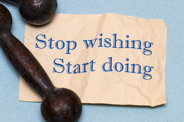 Hör auf zu wünschen, fang an zu tun! motivationssatz auf einem blatt papier mit hanteln und maßband auf blauem hintergrund
