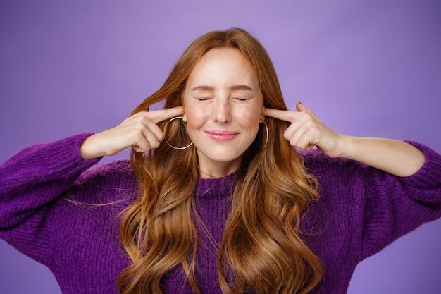 Hör dich nicht. porträt eines lustigen und fröhlichen, gut aussehenden ingwermädchens in violettem pullover, enge augen und ohren mit breitem, glücklichem lächeln, das fröhlich auf lautes rauschen oder geräusch auf violettem hintergrund wartet.