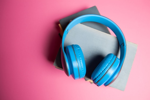 Hörbuch-konzept. bücher und kopfhörer auf rosa hintergrund
