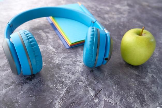Hörbuch-konzept-kopfhörer und notizblock auf weißem hintergrund