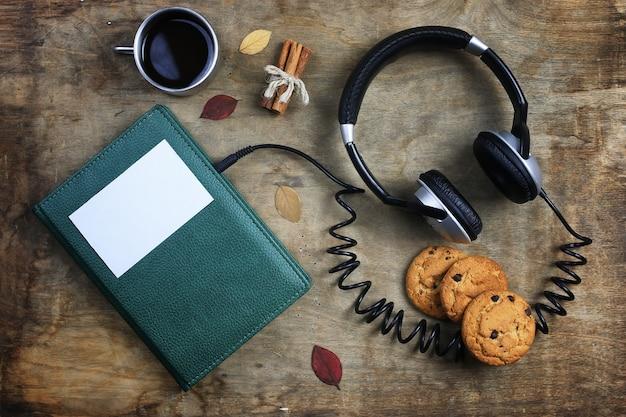 Hörbuch-kopfhörer und buch auf einem holztisch